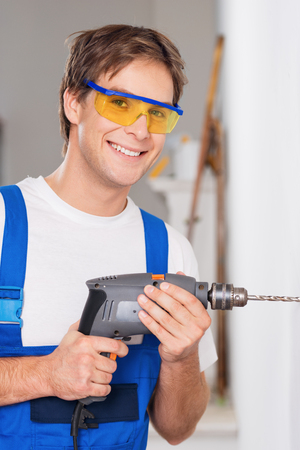 Young smiling repairman in eyewear holding drill and looking at camera Stock fotó
