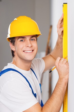 Young smiling repairman in hard hat measuring with the help of builder level
