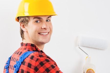 Young smiling repairman in hard hat painting wall by roller and looking at the camera