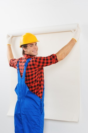 Young smiling repairman in hard hat gluing wallpaper and looking at the camera