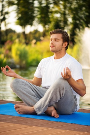Young man maditating with close eyes sitting in lotus pose with a beautiful green scenery of park on background