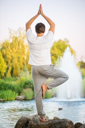 Young man practicing yoga, doing tree pose and turning back upon cmera. With a beautiful green scenery of park on background Imagens - 32863482