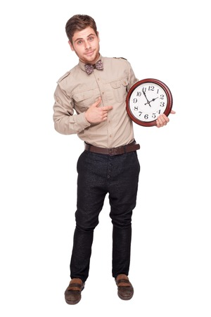 tardiness: Handsome young man holding big clock, isolated on white background. Concept for lateness