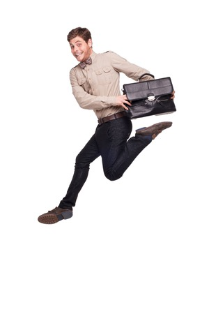 tardiness: Young handsome smiling businessman jumping and holding black briefcase, isolated on white background Stock Photo