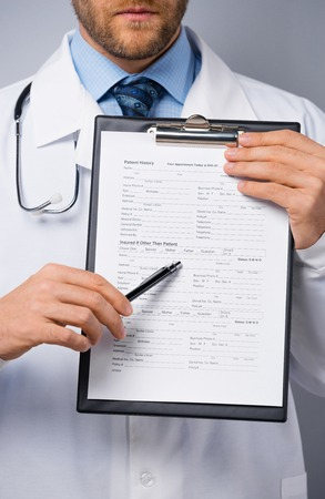 Confident doctor pointing at the folder with insurance form photo