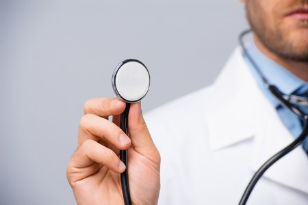 stethoscope isolated on white background: Close-up of serious doctor holding stethoscope in hand on grey background