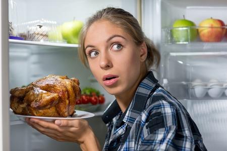 comiendo fruta: Mujer delgada joven con la mirada temerosa de pie cerca de refrigerador abierto y la celebraci�n de pollo frito en la noche Foto de archivo