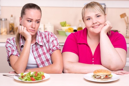 contradiction: Two contradictions. Young woman with well set up figure and young overweight woman eating healthy and junk food