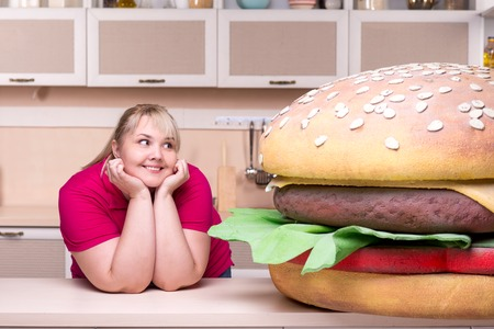 Young smiling overweight woman standing in kitchen and looking at huge hamburger photo