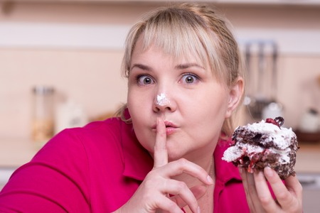 wanting: Young overweight woman wanting to eat secretly big cake
