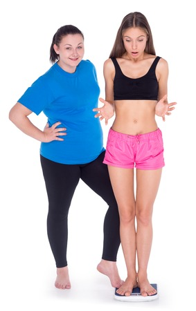 Fun picture of overweight woman discouraging thin young woman standing on weighs and measuring, isolated on white Stock Photo