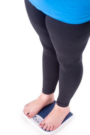 weighs: Close-up of overweight young woman standing on weighs, isolated on white