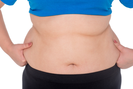 Close-up of fat woman belly, isolated on white. Concept for obesity issue
