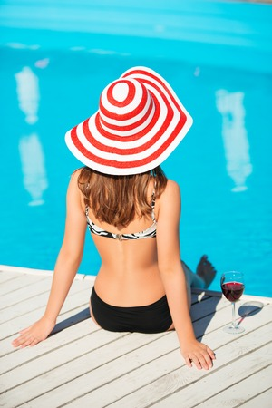 hot day: Back shot of beautiful young woman sitting close by swimming pool with wine glass at hot summer day