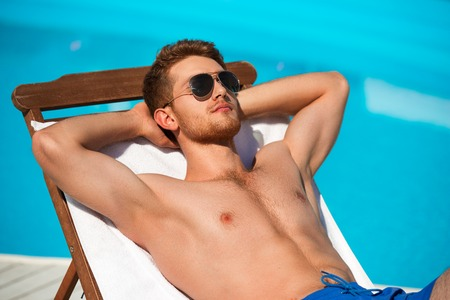 only one man: Handsome young man in sunglasses relaxing while lying on chaise longue close by swimming pool