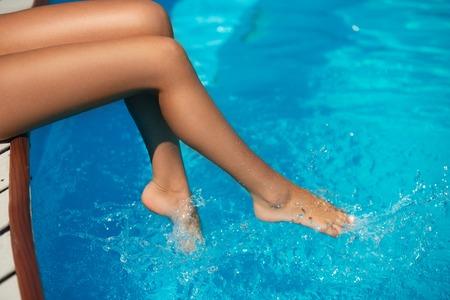 hot summer: Primer plano de hermosas piernas de la mujer delgada que hace el chapoteo del agua en la piscina en el caluroso d�a de verano