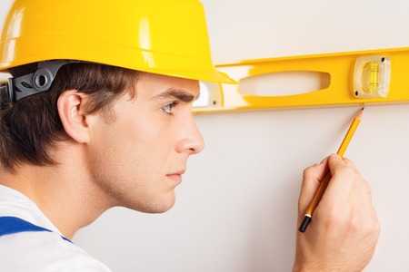 concetrated: Close-up of young repairman in hard hat measuring with the help of builder level