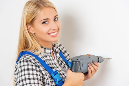 remount: Beautiful young blond in workwear trying to use drill by herself