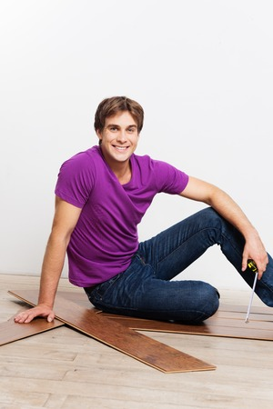 remount: Young handsome man measuring and flooring woodblock at home Stock Photo