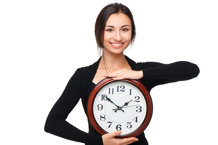 Beautiful smiling young woman holding big clock, isolated on white background. Concept for lateness