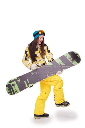 Cheerful young woman in winter clothes holding snowboard and simulating the guitar playing, isolated on white background Stock Photo