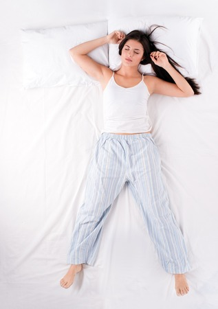 Beautiful young woman sleeping in free fall position on white bed