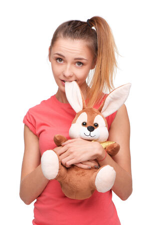 Beautiful teen girl with bunny toy looking at camera, isolated on white background