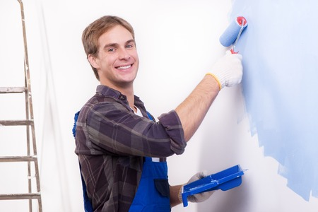 smilie: Young smiling repairman painting wall by roller and looking at the camera