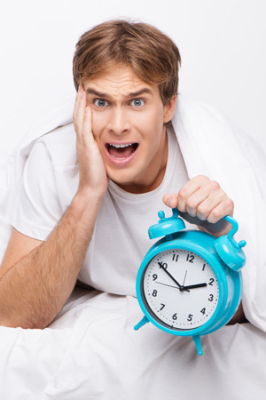 oversleep: Young handsome man screaming and holding blue clock after oversleeping