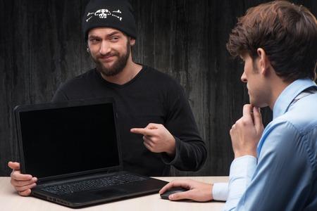 computer hacker: Bearded computer hacker introducing laptop with virus to businessman. Computer hacker concept Stock Photo