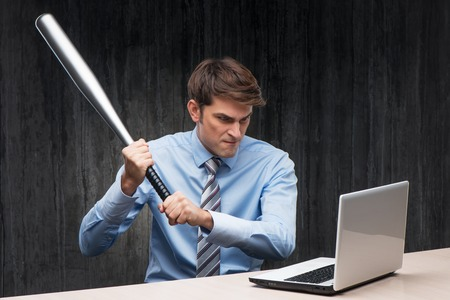 aucasian: Angry businessman with laptop and throwing-stick. Computer hacker concept