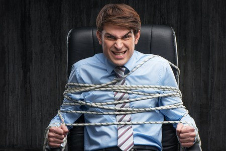 under arrest: White collar angry knotted criminal under arrest Stock Photo