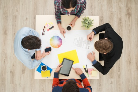 aucasian: Top view of round table with group of busy creative people working on project. Sturt up concept Stock Photo