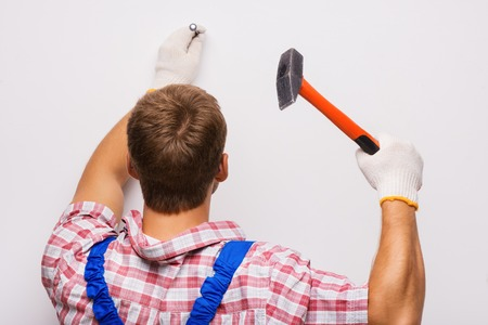 nailing: Back shot of young repairman nailing with the help of hammer Stock Photo