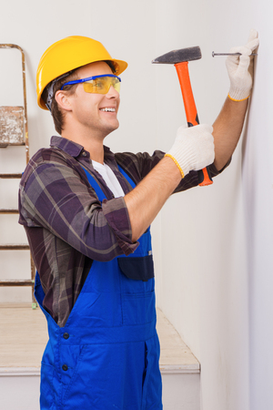 nailing: Young smiling repairman in eyewear and helmet nailing with the help of hammer Stock Photo