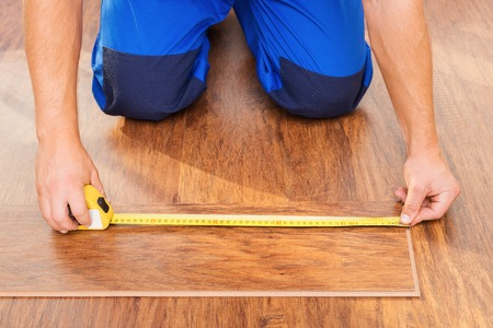 �aucasian: Close-up photo of repairman measuring fabricated wood block flooring Stock Photo