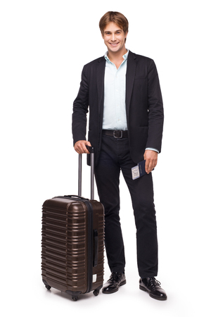 Business traveler smiling and standing with his luggage, isolated on white background