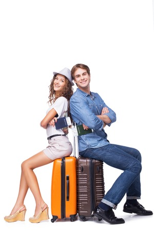 Happy couple is ready to travel, sitting on luggage and holding passports, isolated on white background