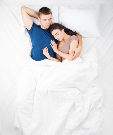 bed sheets: Top view photo of sleeping young couple in big white bed. Man gently hugging his wife. Woman sleeping on his shoulder