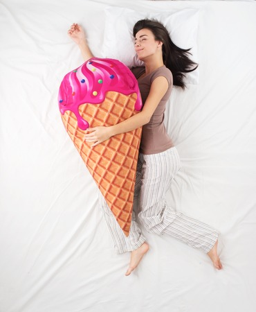 �aucasian: Top view photo of young woman sleeping in an embrace with a large soft ice cream toy and dreaming of sweets. Woman with brown hair