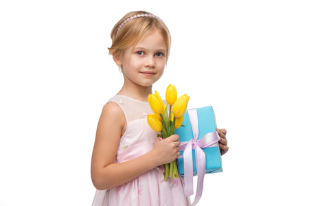 �aucasian: Beautiful little girl wearing pink dress, standing isolated on white background. Holding nice bouquet of yellow tulips and blue present box Stock Photo