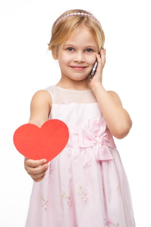 aucasian: Beautiful little girl wearing pink dress, talking by the phone. Isolated on white background. Holding red paper heart. Concept for Valentines Day