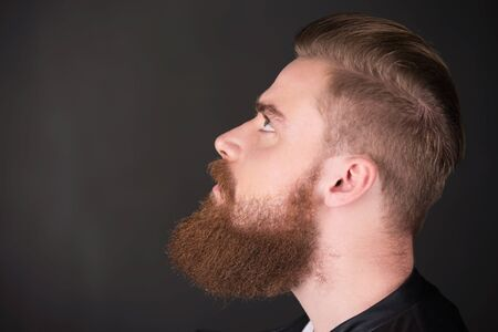 aucasian: Profile of stylish young man with beard looking up