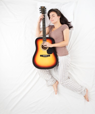 aucasian: Top view photo of young woman sleeping and hudding guitar. Woman with brown hair. Concept for dreams