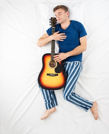aucasian: Top view photo of young man sleeping and hudding guitar. Concept for dreams