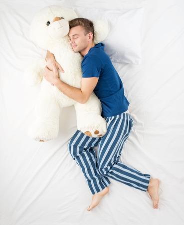 Jonge man slapen in een omhelzing met een grote witte teddybeer. Bovenaanzicht foto
