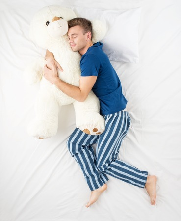 Young man sleeping in an embrace with a large white teddy bear. Top view photo Stock Photo