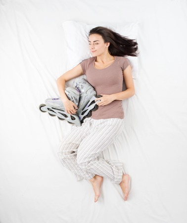 aucasian: Smiling woman sleeping in a big white bed in an embrace with roller skates. Concept for dreams during sleep about sports and hobbies