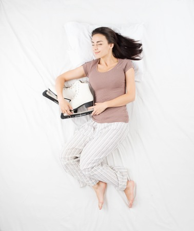 affectionate action: Smiling woman sleeping in a big white bed in an embrace with racing skates. Concept for dreams during sleep about sports and hobbies