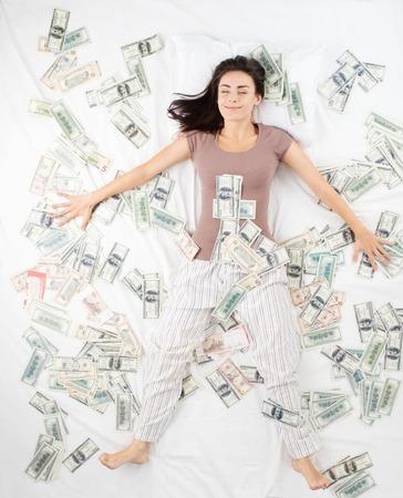 Feliz e sorridente jovem mulher dormindo em uma cama cheia de notas de banco. Conceito para sonhos de ganhar em uma loteria jackpot Banco de Imagens